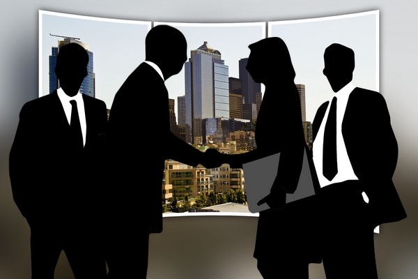 Silhouettes of business man and business woman shaking hands