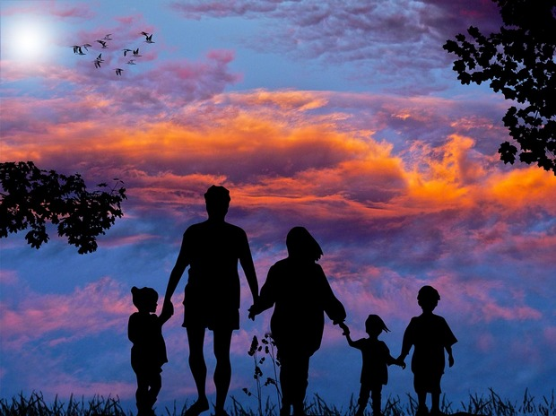 Silhouettes of a family of five against cloudy sunset and birds flying away