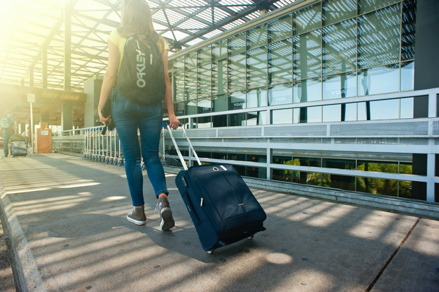 Woman walking towards an airport with strolling luggage.