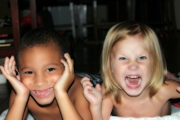 Young boy and a girl making faces at camera